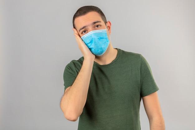 Jovem olhando doente usando máscara facial contra o vírus da coroa, covid-9 toca sua bochecha em branco
