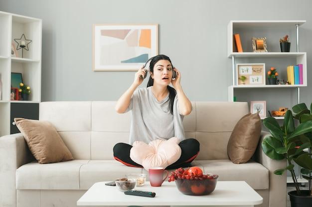 Jovem olhando impressionada com travesseiro usando fones de ouvido, sentada no sofá atrás da mesa de centro na sala de estar