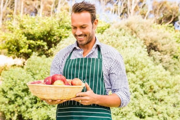 Jovem olhando maçãs na cesta