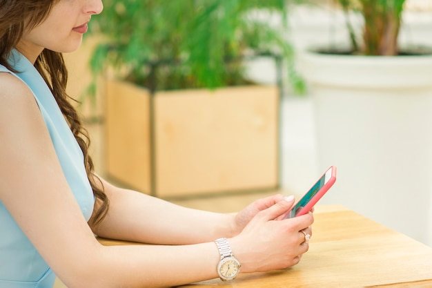 Jovem olhando no smartphone, sentada à mesa