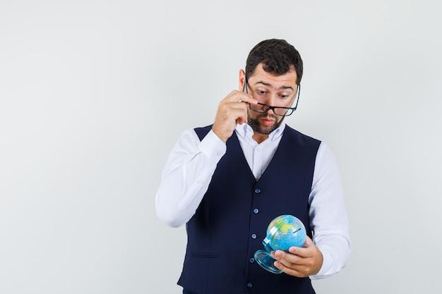 Jovem olhando o globo através dos óculos, camisa, colete e olhar maravilhado