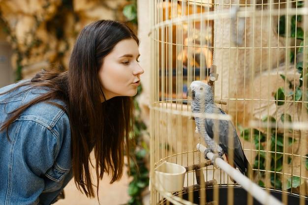Jovem olhando papagaio na gaiola, pet shop. mulher comprando equipamentos em petshop, acessórios para animais domésticos