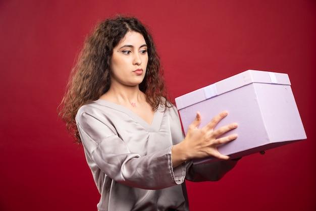 Jovem olhando para a caixa de presente roxa.