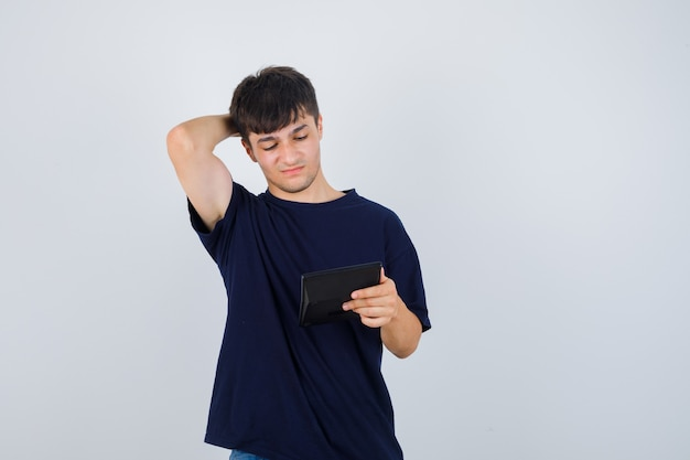 Jovem olhando para a calculadora, mantendo a mão atrás da cabeça em uma camiseta preta e parecendo desnorteado, vista frontal.
