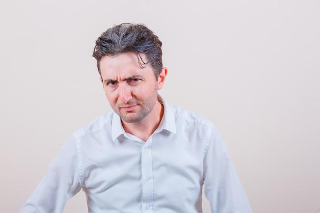 Jovem olhando para a câmera enquanto franze a testa em uma camisa branca e parece desconfiado