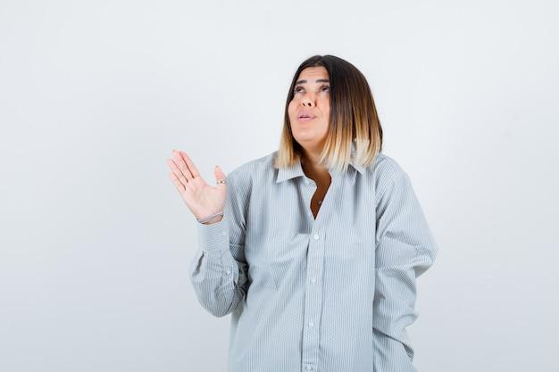 Jovem olhando para cima enquanto espalha as palmas das mãos em uma camisa grande e parecendo pensativa, vista frontal.