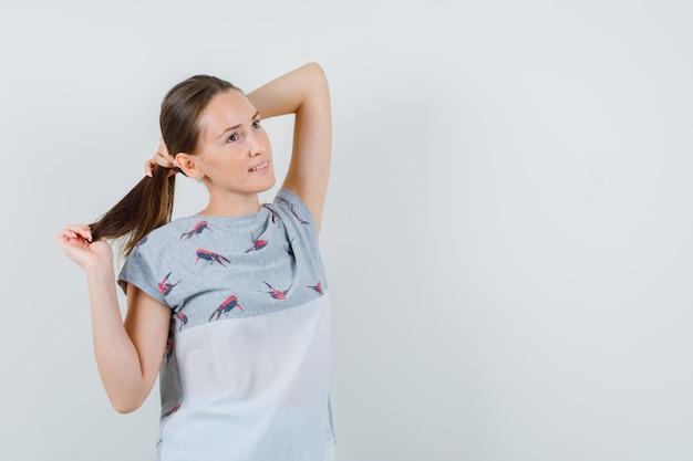 Jovem olhando para cima enquanto segura sua mecha na camiseta e está encantadora. vista frontal.