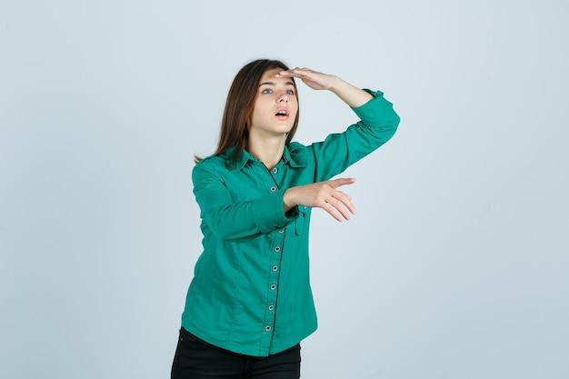 Jovem olhando para longe com a mão na cabeça, apontando para longe em uma blusa verde, calça preta e olhando com foco, vista frontal.