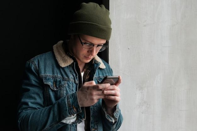 Jovem, olhando para o celular com espaço de cópia
