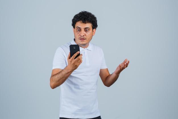 Jovem olhando para o celular em uma camiseta branca e olhando perplexo, vista frontal.