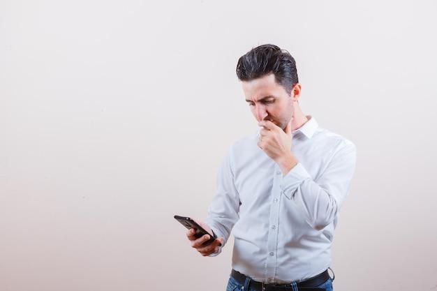 Jovem olhando para o celular enquanto pensa em uma camisa, jeans