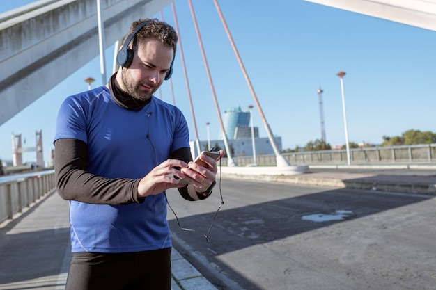 Jovem, olhando para o celular para ouvir música enquanto atravessa uma área urbana