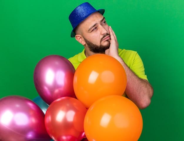 Jovem olhando para o lado satisfeito com um chapéu de festa em pé atrás de balões, colocando a mão na bochecha