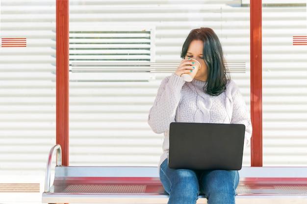 Jovem, olhando para o laptop enquanto bebe café no ponto de ônibus