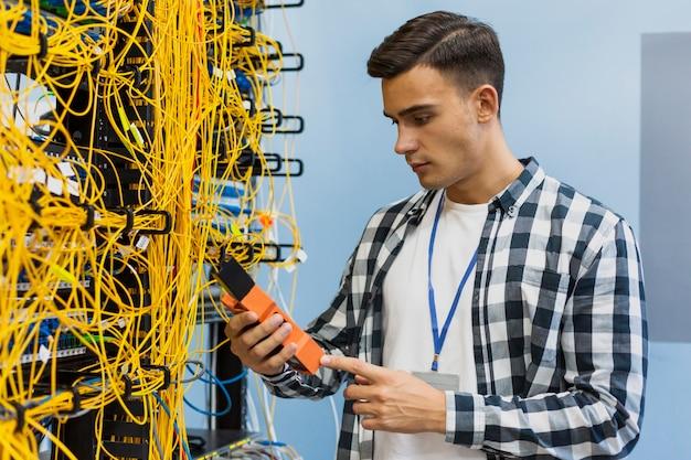 Jovem, olhando para o verificador médio de fibra óptica