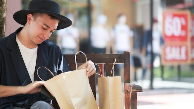 Jovem olhando para sacolas de compras.