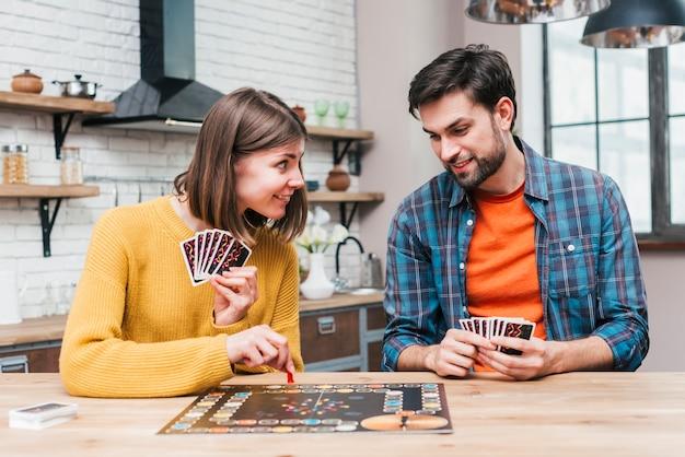 Jovem, olhando para sua esposa jogando o jogo de tabuleiro na mesa de madeira