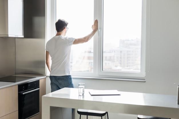 Jovem, olhando pela janela na cozinha