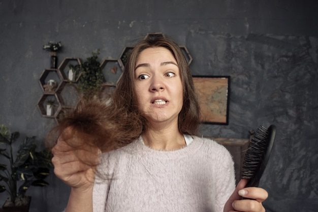 Jovem olhando pente com cabelo, horror e birra, problemas de cabelo