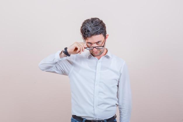 Jovem olhando por cima dos óculos em uma camisa branca, jeans e parecendo em dúvida