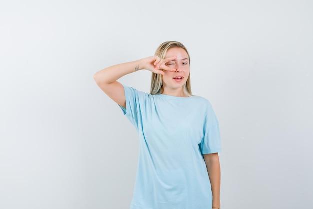 Jovem olhando por entre os dedos em uma camiseta e parecendo feliz isolada