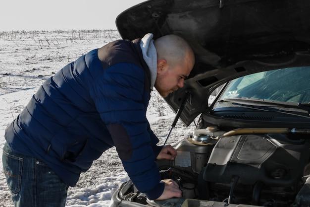 Jovem olhando sob o capô de um carro quebrado em um dia frio de inverno