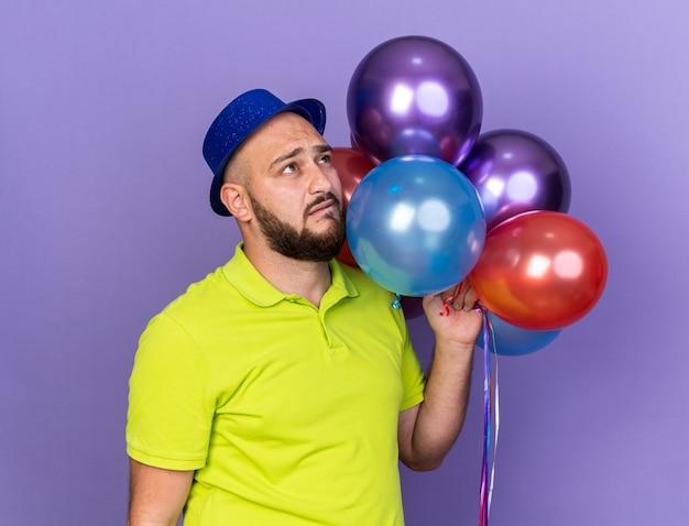 Jovem olhando triste com chapéu de festa segurando balões