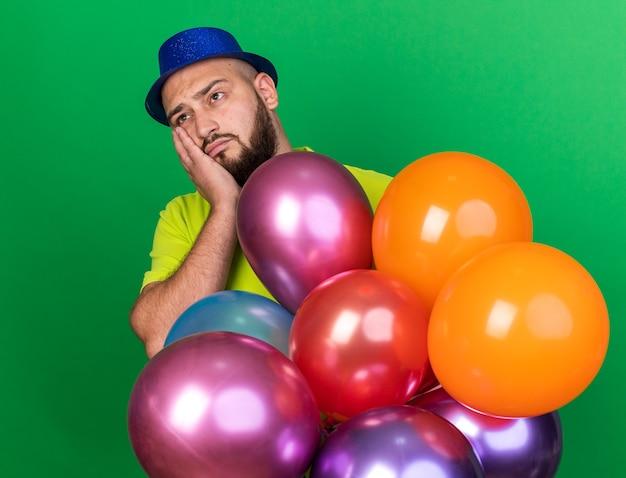 Jovem olhando triste com um chapéu de festa em pé atrás de balões, cobrindo a bochecha com a mão