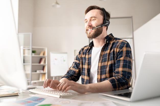 Jovem operador amigável com fone de ouvido pressionando as teclas do teclado do computador enquanto olha para a tela durante a comunicação com o cliente