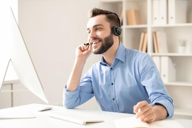 Jovem operador amigável olhando para a tela do computador enquanto fala com clientes por vídeo-chat no escritório