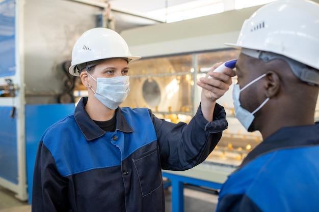 Jovem operador asiático sério usando capacete de segurança usando computador de máquina industrial ao escolher configurações na oficina
