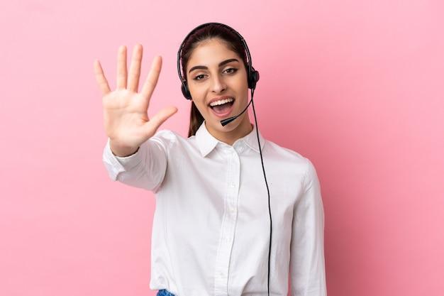 Jovem operador de telemarketing em fundo isolado, contando cinco com os dedos