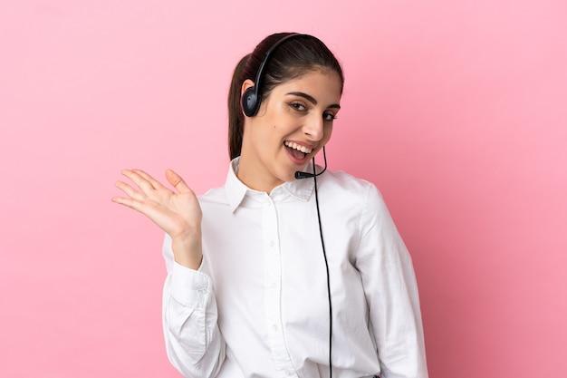 Jovem operador de telemarketing em fundo isolado saudando com a mão com expressão feliz