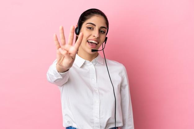 Jovem operador de telemarketing em um fundo isolado feliz e contando quatro com os dedos