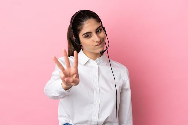Jovem operador de telemarketing feliz em uma parede isolada contando três com os dedos