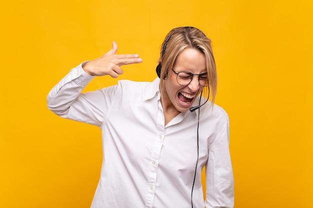 Jovem operador de telemarketing parecendo infeliz e estressado, gesto de suicídio fazendo sinal de arma com a mão, apontando para a cabeça