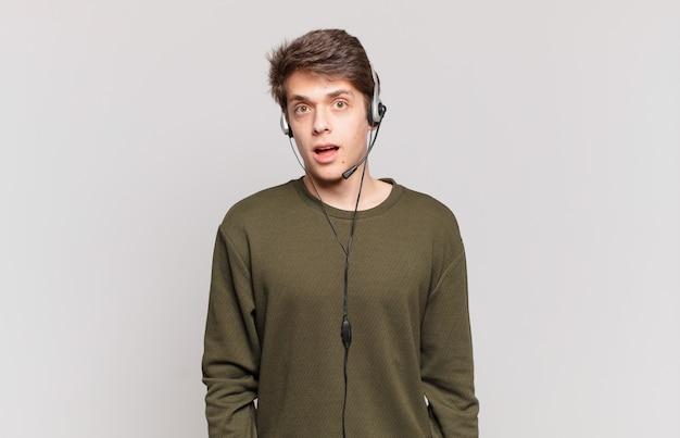 Jovem operador de telemarketing parecendo muito chocado ou surpreso, olhando com a boca aberta dizendo uau