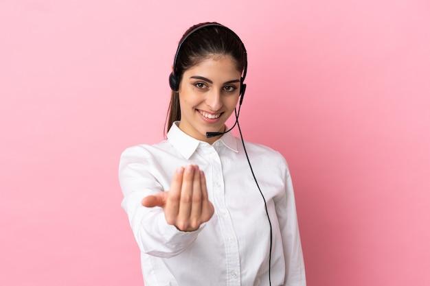 Jovem operador de telemarketing sobre fundo isolado, convidando para vir com a mão. feliz que você veio