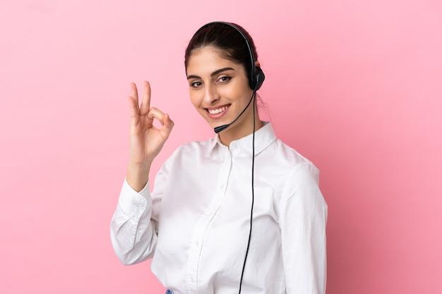 Jovem operador de telemarketing sobre fundo isolado, mostrando sinal de ok com os dedos