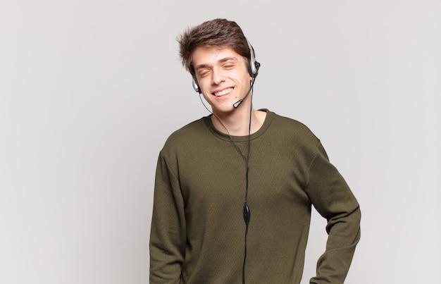 Jovem operador de telemarketing sorrindo feliz com a mão no quadril e com atitude confiante, positiva, orgulhosa e amigável