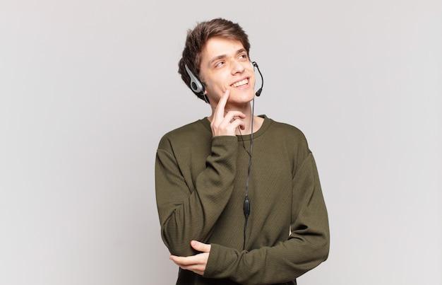 Jovem operador de telemarketing sorrindo feliz e sonhando acordado ou duvidando, olhando para o lado