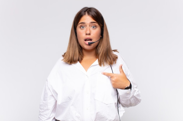 Jovem operadora de telemarketing chocada e surpresa com a boca bem aberta, apontando para si mesma