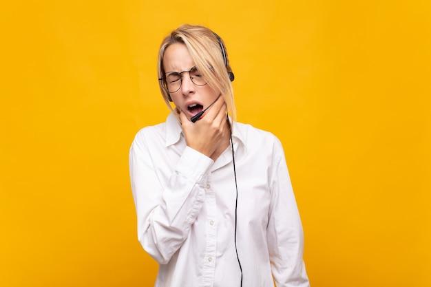 Jovem operadora de telemarketing com boca e olhos bem abertos e mão no queixo, sentindo-se desagradavelmente chocada, dizendo o quê ou uau