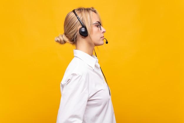 Jovem operadora de telemarketing em vista de perfil, olhando para copiar o espaço à frente, pensando, imaginando ou sonhando acordada