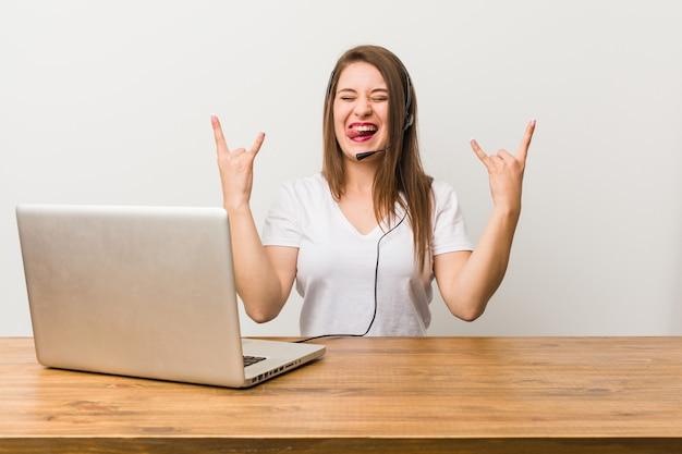 Jovem operadora de telemarketing mostrando gesto de pedra com os dedos