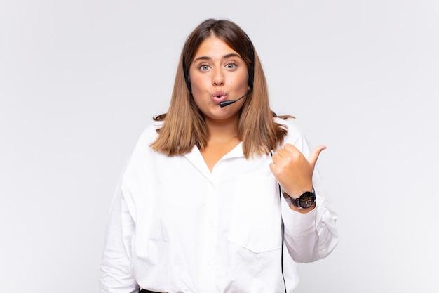 Jovem operadora de telemarketing parecendo surpresa em descrença, apontando para um objeto na lateral e dizendo uau, inacreditável