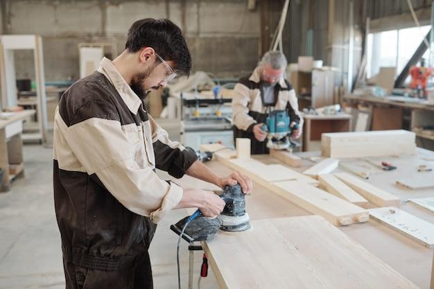 Jovem operário de fábrica usando um moedor para tornar a superfície da peça lisa e preparar a placa de madeira para processamento posterior