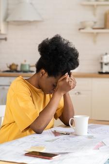 Jovem oprimida, exausta, excesso de trabalho designer afro, cansada de trabalhar com projeto remoto em casa