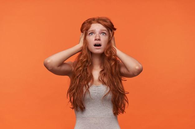 Jovem oprimida, linda mulher de cabelos londrinos, segurando a cabeça com as mãos e olhando para cima com o rosto chocado, posando sobre um fundo laranja em roupas casuais