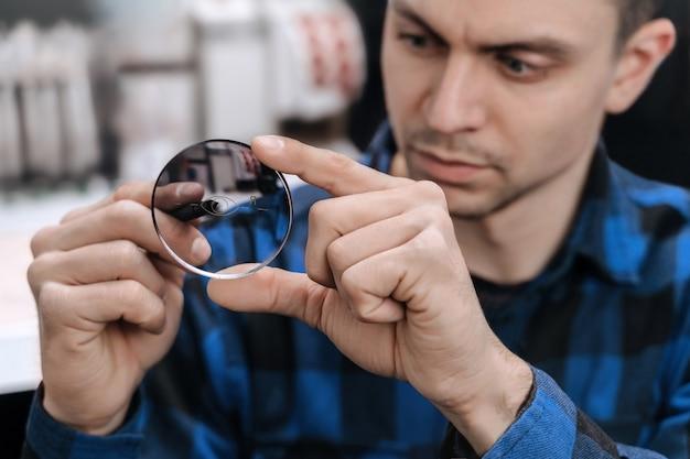 Jovem óptico profissional está trabalhando com lentes em uma oficina óptica usando ferramentas e equipamentos especiais
